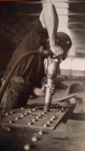 """1940. Un operaio """"ribattino"""" nell'officina carpenteria dell'Ilva."""