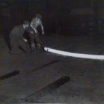 1940. Ilva: operai con un profilato di acciaio incandescente.