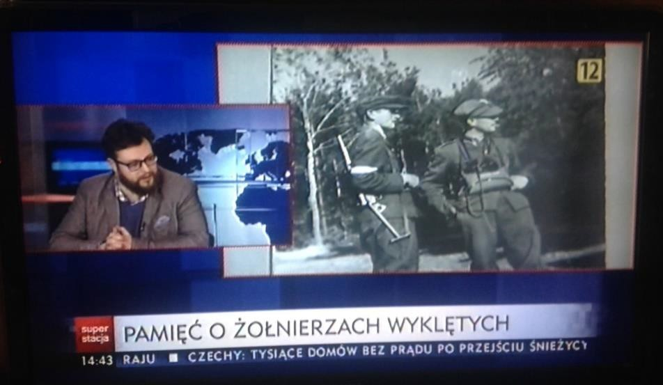 "Fig. 2. Frozen frame from Superstacja' ""Raport"". Guest in the smaller screen and a picture of some unbroken soldiers. The title of this part ""Pamięć o żołnierzach wyklętych"""